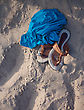 Flip-flops And Blue Fabric Laying Over A Sand Near Sea stock photo