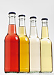 Four Glass Bottles With Colored Drinks stock photo