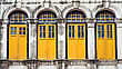 Four Wooden Yellow Windows In Old Building With Arches And Columns stock photo