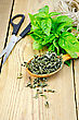 Fresh Green Basil And Dry On The Spoon, Scissors, Ball Of Twine On A Wooden Boards Background stock photography