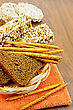 Fresh Rye Bread, Bread Sticks, And Various Crispbreads In A Wicker Tray And The Orange Napkin Against A Wooden Board stock photo