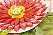 Fresh Sausages, Peppers In Plate And Green Salad Leaves On Bamboo Mat Background