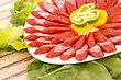 Fresh Sausages, Peppers In Plate And Green Salad Leaves On Bamboo Mat Background stock image