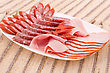 Fresh Sausages In Plate On Bamboo Mat Background stock photography