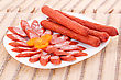 Fresh Sausages In Plate On Bamboo Mat Background stock image