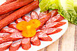Fresh Sausages In Plate And Green Salad Leaves On Bamboo Mat Background