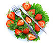 Ration Fresh Strawberries With Fork And Knife On Green Foliage . Isolated stock photo