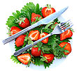Fresh Strawberries With Fork And Knife On Green Foliage . Isolated stock photo