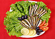 Fried Anchovies On Lettuce Leaves With Lemon, Tomatoes And Olives stock photo