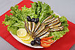 Fried Anchovies On Lettuce Leaves With Lemon, Tomatoes And Olives stock photography