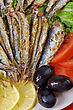 Fried Anchovies On Lettuce Leaves With Lemon, Tomatoes And Olives stock image