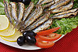 Fried Anchovies On Lettuce Leaves With Lemon, Tomatoes And Olives