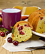 Fruitcake Cherry On A Plate, A Piece Of A Fruitcake On Paper With Cherry Berries, A Napkin, A Knife, A Mug Against A Wooden Board