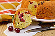 Fruitcake Cherry On A Plate, A Piece Of A Fruitcake On Paper With Cherry Berries, A Napkin, A Knife Against A Wooden Board