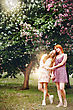 Full Body Portrait Of Two Young Pretty Girls Outdoors. Female Standing Against Spring Flowers Tree At Sunset. Best Friends Concept. Selective Focus