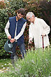Gardener Watering Flowers In A Garden And An Elderly Lady Making Comments As She Watches Him stock photography