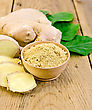 Ginger Powder In A Bowl, Ginger Root, Green Leaves On The Background Of Wooden Board
