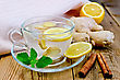 Beverage Ginger Tea In A Glass Cup, Lemon, Cinnamon, Ginger, Mint, Napkin Against A Wooden Board stock photo