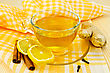 Ginger Tea In A Glass Cup, Two Slices Of Lemon, Cinnamon, Cloves, Ginger Root On A Yellow Napkin And A Wooden Board stock photo