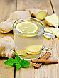 Ginger Tea With Lemon In A Glass Mug, Mint, Cinnamon, Ginger Root On A Wooden Board stock photography