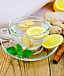 Ginger Tea With Lemon In A Glass Mug, Mint, Cinnamon, Ginger Root On The Background Of Wooden Boards stock photography