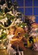 Girl with Bear in front of Christmas Tree stock photo