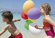 Girl and Boy Running Along Beach with Balloons stock photo