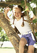 Girl With Braided Hair Sitting In Tree stock photo