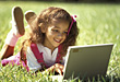 Girl Laying in Grass with Laptop stock photography
