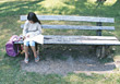 Girl Sitting Alone On Bench Studying stock photo