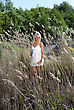 Girl In White Dress Are Standing In Dry Grass At Summer Daylight stock photography