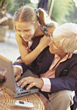 Girl with Grandpa Working on Laptop stock photography