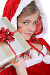Glamorous Child In A Santa's Outfit Offering A Gift stock photography