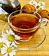 Glass Cup With Herbal Tea, Kettle, Two Cupcakes, Camomile On A Bamboo Napkin stock photography