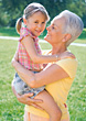 Grandmother Holding Granddaughter In Arms stock photo