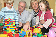 Grandparents Playing With Grandchildren Playing Legos stock photo