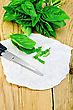 Green Basil Cut With Scissors On Paper On The Background Of Wooden Boards stock photography