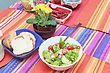 Green Salad In A Stylish White Bowl. With Rocket Leaves Cherry Tomatoes Spanish Onions And Capsicum. Flowers ? Red Pepper And Bread On The Table Too stock photo