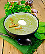 Green Soup Puree In A Bowl With A Spoon On A Napkin And Spinach, Parsley, Croutons, Garlic And Pepper On A Wooden Board stock photography