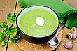 Green Soup Puree In Bowl With A Spoon On A Stand, Napkin, Parsley, Garlic And Pepper On A Wooden Board stock photo
