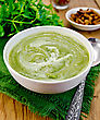 Green Soup Puree In A White Bowl With Spoon On A Napkin, Parsley, Croutons, Peppers On A Wooden Boards Background stock photo
