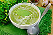 Green Soup Puree In A White Bowl With Spoon On A Napkin, Spinach, Parsley, Garlic On A Wooden Boards Background stock photography