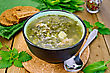 Green Soup Of Sorrel, Nettle And Spinach In A Bowl, Spoon, Bread, Pepper Against A Wooden Board stock photo