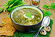 Green Soup Of Sorrel, Nettle And Spinach In A Bowl, Spoon, Bread, Pepper, Quail Eggs On A Wooden Board