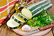 Green Striped Zucchini, Garlic, A Bottle Of Vegetable Oil, Parsley, Napkin, Knife On A Wooden Board