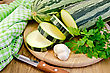 Green Striped Zucchini, Garlic, Parsley, Napkin, Knife On Background Wooden Board