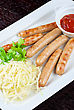 Sausages Grilled Sausages With Cabbage, Greens And Tomato Sauce On White Plate stock image
