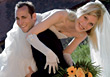 Wedding Groom Carrying Bride Over His Shoulder stock photo