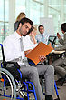 Group Of Business People In A Meeting Room, One Of Them In A Wheelchair. stock photography