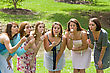 Group of College Girls Blowing Dandelion Seeds